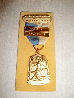 This is a 1958 first place rifle shooting award for shooting while kneeling. It is in the original box.  This medal was made by a company out of Attlerboro Falls, Mass. The... #trophy