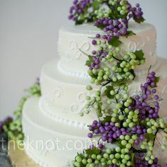 Candied green and purple grapes draped down the side of the vanilla buttercream cake.  Like details on cake and pearls design on bottom each layer