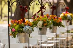 Hanging flower buckets for the aisle, recyclable as table centerpieces