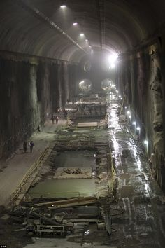 Future gateway: New York construction workers are seen dwarfed by four tunnels easily seen running into the city's future concourse that is about five-football fields long and eight-stories high http://www.dailymail.co.uk/news/article-2275380/New-York-City-expanding-nations-biggest-transit-hub-16-stories-beneath-Grand-Central-Terminal.html#