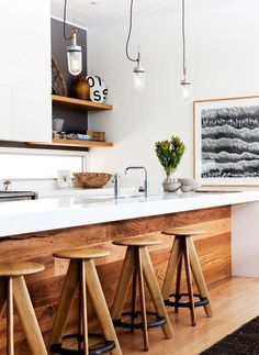 Rustic + modern. A weird combination? I don't think so. The two can converge so beautifully!  Wood stools and island siding add a good dose of wooden charm to your modern kitchen. Warm wood panels and wooden bar stools are a wonderful way to add warmth and a welcome spot to your kitchen.