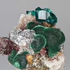 Tsumeb Mine, Otavi Highlands, Namibia - A nice combination specimen with roundish aggregates of intense green malachite, saddle-shaped greyish dolomite, an incomplete crystal of dioptase, brownish-orange perimorphs of an unknown mineral and prismatic quartz.