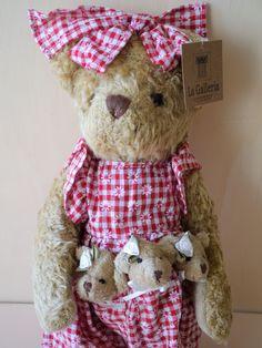 Bär im roten karierten Kleid. Das Kleid ist mit Gänseblümchen gemustert. 3 kleine Bären in der Tasche.