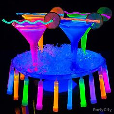 """Use neon bright martini glasses and black light for this gorgeous Glow-Tini cocktail idea. Use your favorite gin and tonic martini recipe and display them on a white stand with white paper shred. Be sure to get the type of glow stick that has an open """"hook"""" on the end, and you can easily hang them around the rim of the cake stand."""