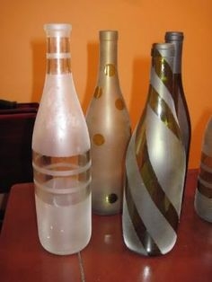 Take the label off of wine bottles, put painters tape in different designs, spray with spray paint, let dry, and peel off the tape. This would be a good idea for a centerpiece idea! A few at each table with different designs by perla marie