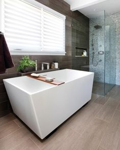 This is outstandingly beautiful! I love a bathroom with a stand alone tub and a rustic feel of the flooring Credits: freshome.com #Modernyze