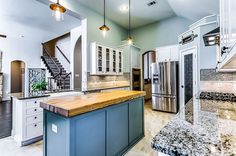 Traditional kitchen with white cabinets, blue island with wood counter and bianco antico granite countertops