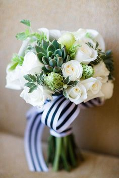 A white and green bouquet with roses and succulents, wrapped with a preppy striped ribbon | Brides.com