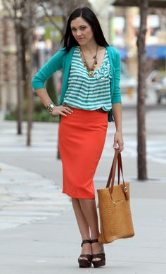 complementary colors of orange and teal. Clothing includes a Blu Peper teal striped top, Active Basic teal cardigan, Alythea coral skirt with belt,Bohme sandal, Bohme camel tote, and Bohme necklace, Clothing from Bohme Boutique.