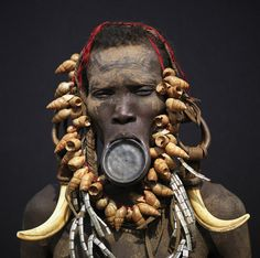 (Eric Lafforgue | Woman with lip plate - Ethiopia)  Piercing, labret, and and lip plates are a strong part of the Mursi and Surma -Suri culture. These traditional adornments are worn by almost all the adult Suri women. When a woman becomes engaged to be married, usually in her teens (around 14 or 15), she disappears from village life to live in her family hut. The gap between her front lip and the flesh below is pierced and gradually stretched.