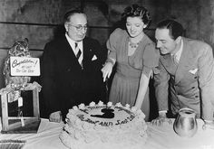 """Louis B. Mayer and William Powell watch as Myrna Loy cuts her birthday cake on the set of """"Another Thin Man"""""""