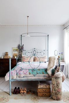 Love the pastel metal bed frame juxtaposed to the shaggy blankets and wooden dresser.