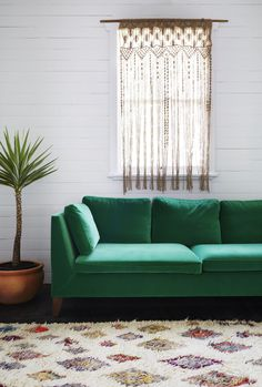 A colourful Moroccan Talsint rug 'Tiny Cities' looks amazing with a green couch and simple indoor plant.  Rug available from http://tigmitrading.com/collections/rugs/products/tiny-cities-talsint