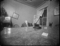 A homicide victim seated at a living room or kitchen table, 1916-1920