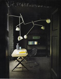 on the dark side. black brick walls, black floor, vintage industrial lamp (Elle Decoration UK)