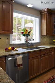 Kitchen remodel by Renovisions. Decorative tan and black tile backsplash. Granite countertops with matching window sill. Natural Cherry cabinets with under cabinet lights. Stainless steel appliances and sink. Recessed lights.