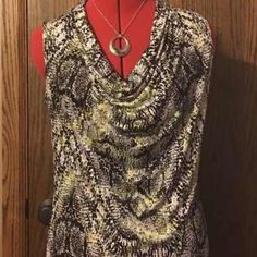 "Like new beautiful sleeveless tunic This beautiful tunic has hints of lime mixed with white and black for a gorgeous and interesting pattern. It is very soft and comfortable. Can be worn alone or with a sweater or blazer, making it a staple for your wardrobe year round. It is longer in length to cover up the ""muffin top"" and has a cowl neck. Can be worn many different ways. Worthington Tops Tunics"