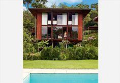 Perto de São Paulo e cercada pela vegetação, a casa de 220 m² é o plano de vida concretizado de um casal. A fachada foi feita de módulos de madeira e paredes de vidro.