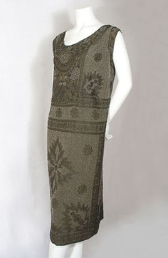 Beaded silk crepe flapper dress, 1920s. The dress is almost totally covered in beads! The beading is a work of costume art: the monochromatic design is elegant and subtle. A combination of clear crystal beads and jet black beads against a brown silk ground was used. The jagged geometric forms (black beads)—suggestive of lightening or energy—surround a central hatched circle. Radiating out from the circle are schematic arrows (clear crystal beads). The design is both exciting and subtle…