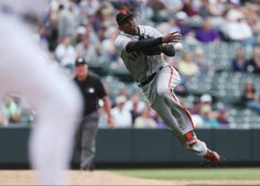 San Francisco Giants third baseman Joaquin Arias makes the throw to put out Colorado Rockies' Nolan Arenado to end the eighth inning of the Giants' 12-10 victory in 11 innings in a baseball game in Denver on Wednesday, April 23, 2014. (AP Photo/David Zalubowski)