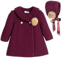 Baby girls burgundy red traditional heritage style knitted coat and bonnet set by Foque. This charming styled outfit is ideal to be worn as a pram coat on colder days. It has a soft feel and a ribbed collar and trim, with popper fastening and a rabbit fur pom-pom on the side. The matching bonnet has ribbon ties that secure in a bow under the chin.