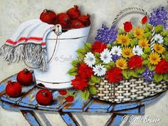 Stella Bruwer white enamel bucket with pomegranates and white towel with red stripe wicker basket of summer flowers  on blue slatted table