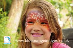 Blue Orange Images facepainting #Watford, girl face painted with a rainbow design and white daisies and #glitter.