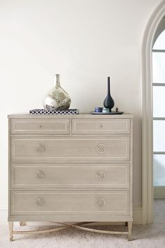Luxurious, yet designed with modern sensibilities in mind, this drawer chest illustrates a perfect harmony between design and function. The top two drawers feature drop fronts and wire management holes to easily connect media devices to a TV. Details like a metal tubular base in a Radiant Nickel finish and a stainless steel metal inlay on the chest top provide elegant touches. A Heather Gray finish balances the glamorous detailing for an effortlessly sophisticated transitional look.