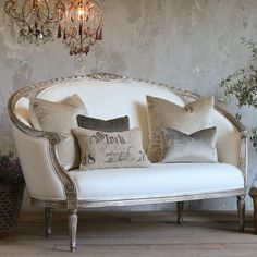 French settee in natural linen with a charming romantic chandelier.