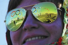 The Olympic rings are reflected in the sunglasses of a volunteer at the Olympic Park at the 2014 Sochi  Winter Olympic Games (Brian Snyder/Reuters)