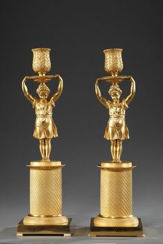 A pair of candlesticks in ormolu and chiselled bronze with a young girl forming the stem, standing up on a circular pedestal chiselled with twisted patterns, above a square plinth...