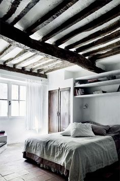 Rustic bedroom featuring beautiful exposed wood beams, ceramic tile flooring and gray and beige washed linen bedding - Neutral Home Ideas & Decor
