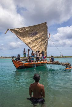 A young boy watches the men of his community embark on a sail, eagerly awaiting…
