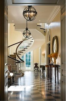 Drop dead gorgeous foyer by architect Allan Greenberg and interior design firm Cullman Kravis. Deep longitudinal space has a surprising setback spiral staircase, as opposed to the more obvious traditional staircase with a landing off to one side. Two black orb chandeliers one behind the other lead your eye through the space, as do the french doors at the end of the French doors. Hate the floor.