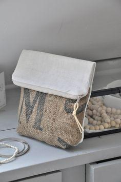 Pochette à rabat réalisée en toile de jute imprimée et lin écru anciens tous les deux. Doublure intérieure en coton teint en gris bleuté Fermeture ...
