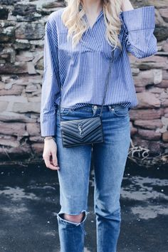 Charlotte Lewis Fashion Blogger with Saint Laurent bag and denim outfit wearing a striped blue flared sleeve shirt