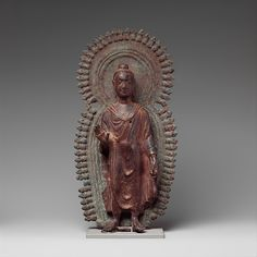 This image was likely used for personal veneration. The Buddha wears a typical Gandharan-style robe while his hair is reminiscent of images from Swat and Kashmir. Although the combined radiate halo and mandorla appears in Gandhara, this exact motif is found at the Afghan site of Bamiyan. Buddha with Radiate Halo and Mandorla  Date:6th century Culture:Pakistan (ancient region of Gandhara) Medium:Brass Dimensions:H. 11 1/2 in. (29.2 cm); W. 5 1/2 in. (14 cm) Classification:Sculpture