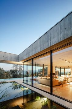 Large floor-to-ceiling windows provide views of the swimming pool and the smaller pools between the two volumes. High Building, Building A House, Raised House, Clad Home, Cork Tree, Floating Garden, Latest House Designs, Concrete Houses, Exposed Concrete