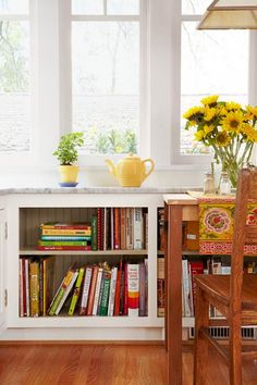 Create a cookbook nook like this one: Open shelves were built at the sunny end of this kitchen with a small table nearby