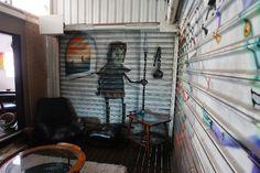 """As portas corrediças que """"cercam"""" o estar na cobertura podem ser totalmente abertas, mas quando fechadas têm seu peso quebrado pelos grafites assinados pelo artista Crânio (Fabio Oliveira)"""
