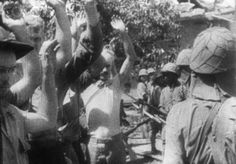 Original caption: Corregidor, Philippines: A scene from captured Japanese film showing Japanese soldiers holding bayoneted rifles as heroic defenders of Bataan Corregidor file past them with arms held high. This was the last United States day on Corregidor-until recapture the Island Fortress. This came after Japanese bombings had destroyed the water system and depleted supplies that made the surrender a necessity.
