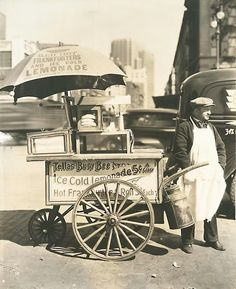 Vendor stands next to his Tellas Busy Bee cart, advertising 'Red Hot Frankfurters and Ice Cold Lemonade' traffic a blur in the background. The photo was taken on April 8, 1936 at West S…
