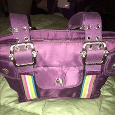 Franco Sarto Handbag Used once. Dark purple Franco Sarto bag. Silver hardware throughout the bag. Beautiful silver buckles on both the front & the back of the bag. Hot pink liner with lots of zipper pockets on the inside. Zipper closure of the bag. Great condition! Not looking to trade. Franco Sarto Bags Shoulder Bags
