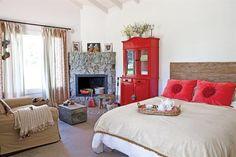 En el dormitorio principal, se proyectó una chimenea en esquina. Banquito de tapizado en barracán bordado (Carolina Hardoy). Sofá de dos cuerpos con manta tejida en el apoyabrazo. Un baúl antiguo rescatado de un galpón..