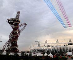 """È iniziato il """"countdown"""" della cerimonia d'apertura delle Olimpiadi di Londra 2012. Sull'Olympic Park sono passate le Red Arrows, le frecce tricolori inglesi, che hanno lasciato una scia di fumo rosso, bianco e blu, i colori della """"union jack""""."""