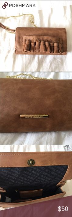 """Steve Madden Cognac Crossbody/Clutch NWT Steve Madden Cognac Crossbody/Clutch.  Could be used as crossbody or clutch. Gold tone chain strap. Body is vegan leather, tassels are 100% genuine suede. New with tags. Never used. One small spot show on 3rd pic probably from logistics. Can't tell as that part of the task is more to the backside.  10""""  x 5.5""""  X 2"""".   23"""" strap drop Steve Madden Bags Crossbody Bags"""