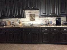 The once white cabinets were painted with bittersweet chocolate paint from Benjamin Moore and the custom backsplash was done with travertine and glass tiles.