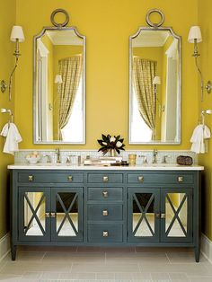 yellow wall, navy blue console, white marble counter top, silver individual mirrors, petite sconces, his and hers