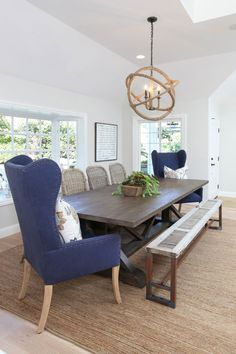 Great mixed dinning seating: trestle table, blue high-back chairs, bench, & rattan chairs. Hemp wrapped orb chandelier. Sisal rug.