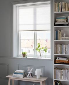 A blind is drawn halfway down in a window with plants on the window sill.